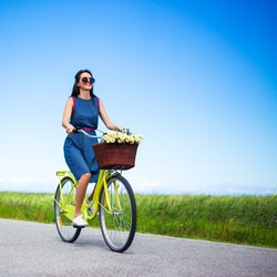 travel concept - woman riding vintage bicycle with basket in countryside over blue sky background