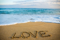 travel concept - word love written in golden sand on the beach