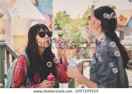 Travel Concepts. Beautiful girl is playing soap bubble fun. Asian girls are relaxing travels. Asian girls blowing bubbles into the air. Beautiful girl takes a break in playing bubble activities.