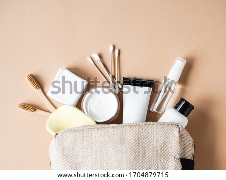 Travel cosmetic bag with the necessary means to care for women's skin. Cosmetics, dry shampoo, cotton buds, toothbrushes next a cosmetic bag on a beige background. top view  Stock foto ©