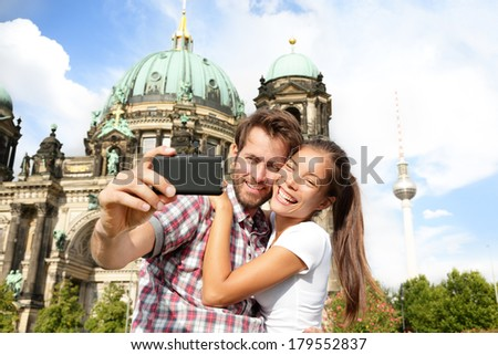 Travel couple selfie self portrait, Berlin, Germany. Happy tourists people in front of Berlin Cathedral / Berliner Dom with Fernsehturm / Berlin TV Tower in the background. Asian woman, Caucasian man.