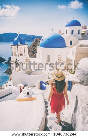Travel destination europe tourist girl walking in Santorini at the three blue domes, famous Greek landmark. Oia village, Santorini island, luxury vacation.