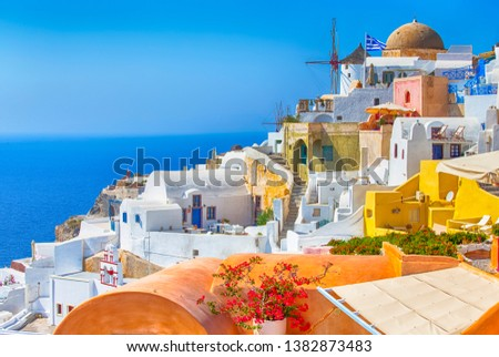 Travel Destinations. Picturesque Cityscape of Oia Village in Santorini Island Located on Volcanic Calderra at Daytime. Traditional Windmills on Background. Horizontal Image