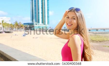 Travel Europe summer holiday girl enjoying Arrecife, Lanzarote, Canary Islands. Sun getaway woman smiling with sunglasses on her head. Foto stock ©