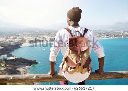 Travel for life concept. Outdoor shot of unrecognizable contemplating black tourist sitting at wooden beam of sightseeing platform admiring seaside view of resort city, carrying leather backpack