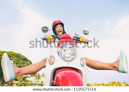 Travel fun funny tourist carefree driving scooter on summer road trip. Screaming Asian girl goofing around with legs up riding motorcycle.
