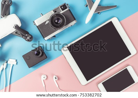 Travel gadgets flat lay on blue and pink background for travel concept