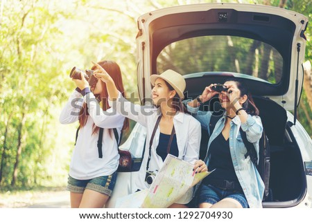 Travel group asian woman traveler sitting on hatchback car for trip adventure road with outdoors forest in vacations and holiday trips. Travel Concept