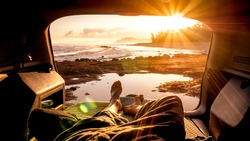 Travel guy laying in the auto van and enjoying sunrise from the window with amazing landscape. Best wake up during adventure trip with amazing feeling. Concept of nature and having freedom in holiday
