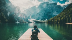 Travel hiker taking photo of Lake Braies (Lago di Braies) in Dolomites Mountains, Italy. Hiking travel and adventure.