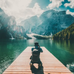 Travel hiker taking photo of Lake Braies (Lago di Braies) in Dolomites Mountains, Italy. Hiking and outdoor adventure lifestyle.