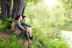 travel, hiking, backpacking, tourism and people concept - smiling couple with backpacks resting on river bank in nature on river bank