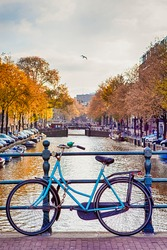 Travel Ideas. City of Amsterdam. Traditional Dutch Bicycle In Front of The Canal Fence in Amsterdam. Vertical image Composition