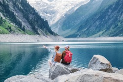 Travel image. Travelers team look on the mountain landscape. Travel and active life concept with team. Adventure and travel in the mountains region in the Austria