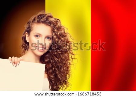 Travel in Belgium concept. Pretty blonde girl against the Belgium flag background ストックフォト ©