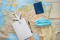 Travel in epidemic quarantine notes template. Table top view with map, plane, notebook, face mask, passport, medical gloves. personal hygiene and protection items in tourism theme. restrictions