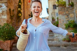 Travel in Italy. happy stylish middle aged traveller woman with straw bag sightseeing in Pienza in Tuscany, Italy.