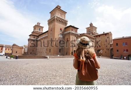 Travel in Italy. Rear view of traveler girl walking towards Este Castle (Castello Estense) of Ferrara, Italy. Photo stock ©