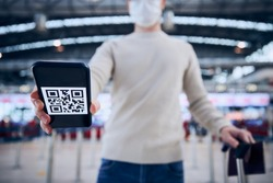 Travel in new normal. Man wearing face mask and holding smart phone with QR code at airport. Themes verification of immunization after vaccination with covid-19 and flying rules during pandemic.