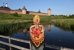 Travel in Russia. Russian tourist woman in traditional national Pavlovo Posad folk shawl, scarf. Old Kremlin in Suzdal town, Vladimir region, Russia. Summer tourism in Russia. Kamenka river. Landmark