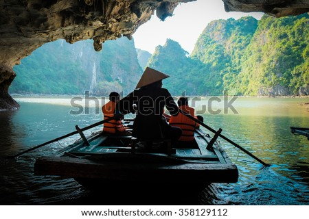 Travel in Vietnam,A young girl paddle a bamboo boat for tourist in the beautiful bay.