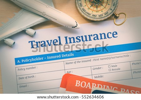 Travel insurance application form on a wood table with a white model airplane, boarding pass and a compass. Travel insurance is intended to cover medical expenses, trip cancellation, lost luggage, etc #552634606