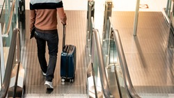 Travel insurance concept. Asian man tourist carrying suitcase luggage and digital tablet walking down escalator or moving walkway in airport terminal.