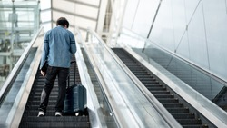 Travel insurance concept. Asian man tourist or passenger man carrying suitcase luggage and digital tablet on escalator in airport terminal.