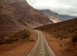 Travel into the unknown. Empty road in the Andes mountain range desert, on the way to Aconcagua mountain in Mendoza, Argentina.