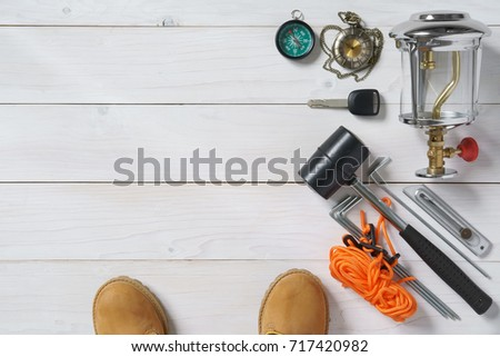 travel item frame for holiday relax and adventure with knife, boots, lantern, car key, compass, clock, rubber hammer, anchor and tent rope on white vintage wood floor or table top view for background #717420982