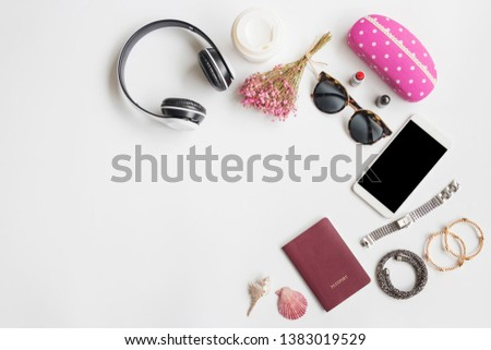 Travel items with women's accessories on white background