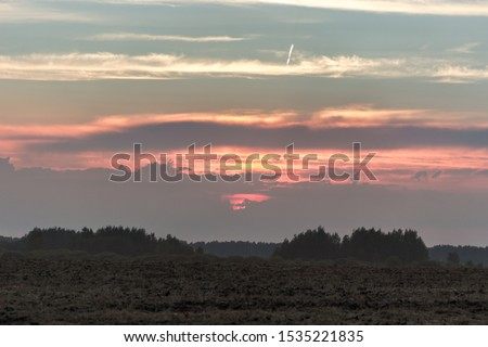 travel, landscape and nature of Russia. Yellow golden orange dramatic dawn at dawn or dusk over endless fields, hills, meadows. The sun rises in the morning above the horizon