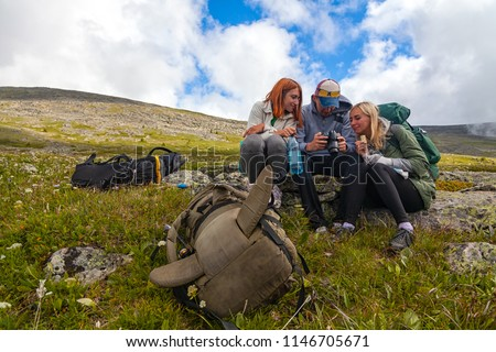 Travel Lifestyle and survival concept rear view. Hiking women  and men with backpack  enjoying the trekking, sit on a halt and looks at the pictures taken on  camera in the background  mountains.