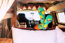 Travel lifestyle with minivan and vanlife style - unrecognizable girl inside a retro camper - feet with socks visible from a lay down unrecognizable people - happy lifestyle young people journey