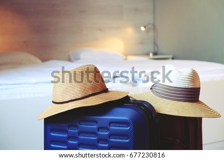 Travel luggage with vacation hat in the hotel room. Same sex lesbian couple traveling concept. Wooden wall background, soft intimate light, white sheets. Close up, front view.