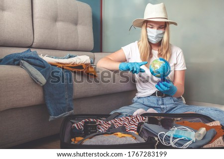 Travel. masked girl puts her things in a suitcase and dreams of rest, traveling after quarantine, blocking, covert 19. Staycation.local travel.Tourism after opening borders, end of quarantine