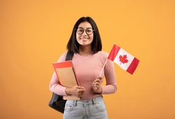 Travel, modern education and student exchange. Young cheerful asian woman in glasses with notebooks, backpack holding small flag of Canada, isolated on beige background, studio shot, empty space