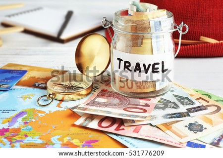Travel money savings in a glass jar with compass, map and hat #531776209