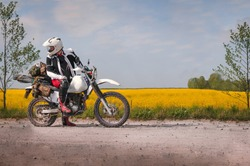 travel motorcycle off road Motorcyclist gear, A motorcycle driver looks, concept, active lifestyle, enduro, in the background a field of yellow flowers