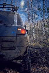 Travel off-road on a forest road in a blue 4x4 car. 4x4 SUV all dirty pulls back from a dead end