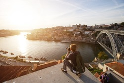 Travel photographer doing pictures of sunset above river in Porto, Portugal. Europe traveling