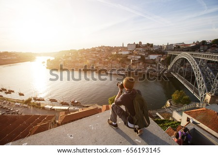Travel photographer doing pictures of sunset above river in Porto, Portugal. Europe traveling  #656193145
