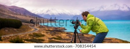 Travel photographer man taking nature video of mountain landscape at Peter's lookout, New Zealand Banner. Hiker tourist professional videographer on adventure vacation shooting slr camera on tripod. #708354454