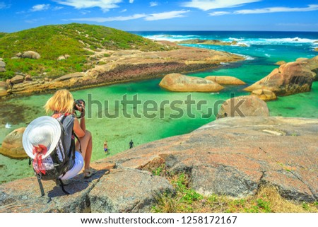 Travel photographer takes shot of Elephant Rocks in William Bay National Park near Denmark, Western Australia. Female tourist takes pictures with professional camera of Great Southern Ocean coastline.