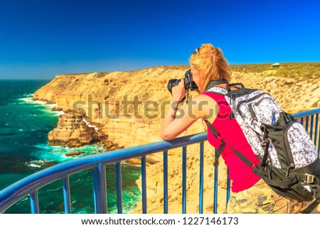 Travel photographer takes shot of Natural Bridge lookout in Kalbarri National Park, Western Australia, Australian Outback. Female tourist takes pictures with professional camera of Indian Ocean cliffs