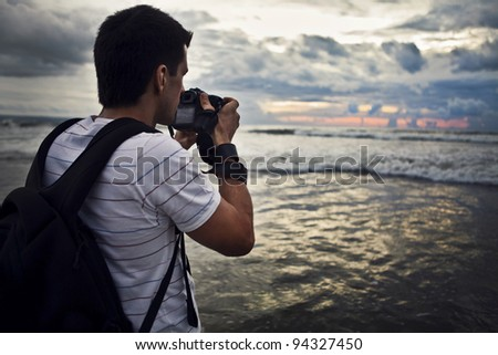 Travel photographer with digital camera making photo of the nature.