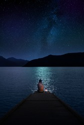 travel photography, a caucasian lonely boy rear view sits on the pier with a flashlight on the background of the night sea, silhouettes of mountains and the starry sky
