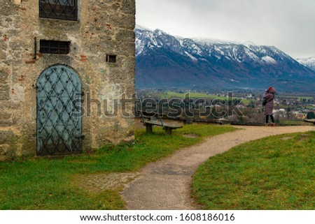 travel photography in Central European region near medieval castle destination site with snowy mountain ridge peaks landscape background and woman taking photo