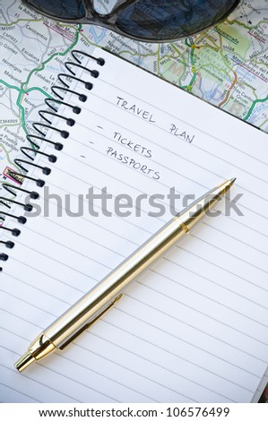 Travel plan concept with notebook, writing, sunglasses, map and ballpoint pen