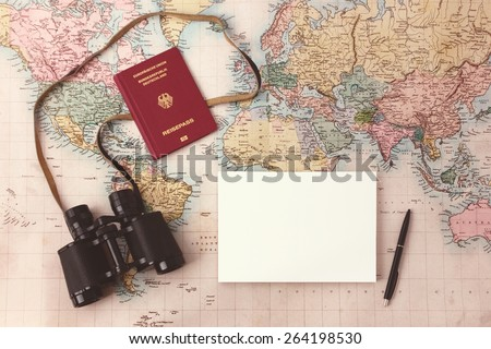 Travel planning - map with passport, notepad, pen and binoculars
